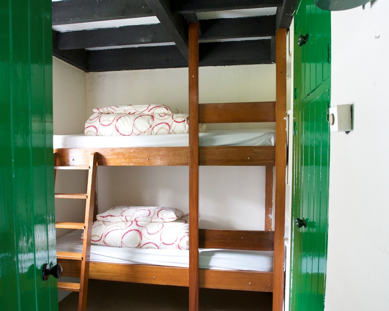 Corofin Bunk Room with ceiling beams and wood cabinets