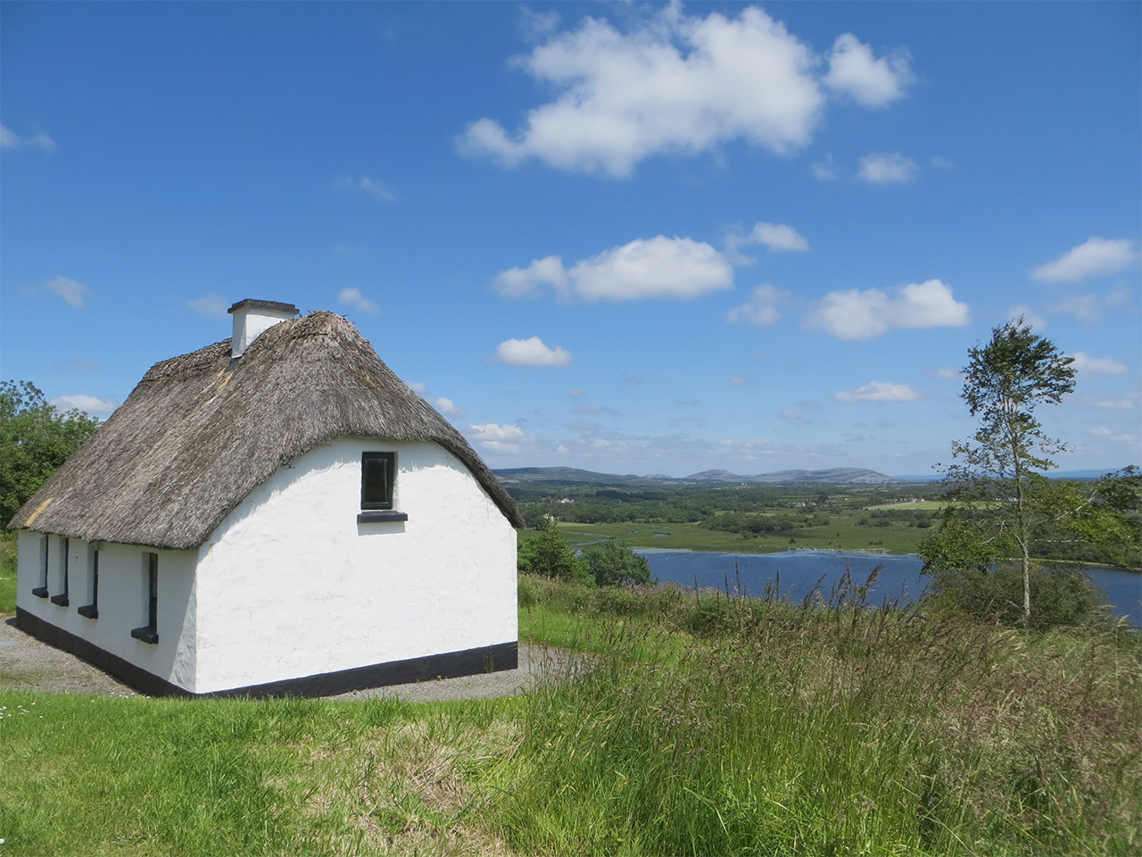 Side of a Thatched Cottage overlook Lake Inchiquin with blue skies