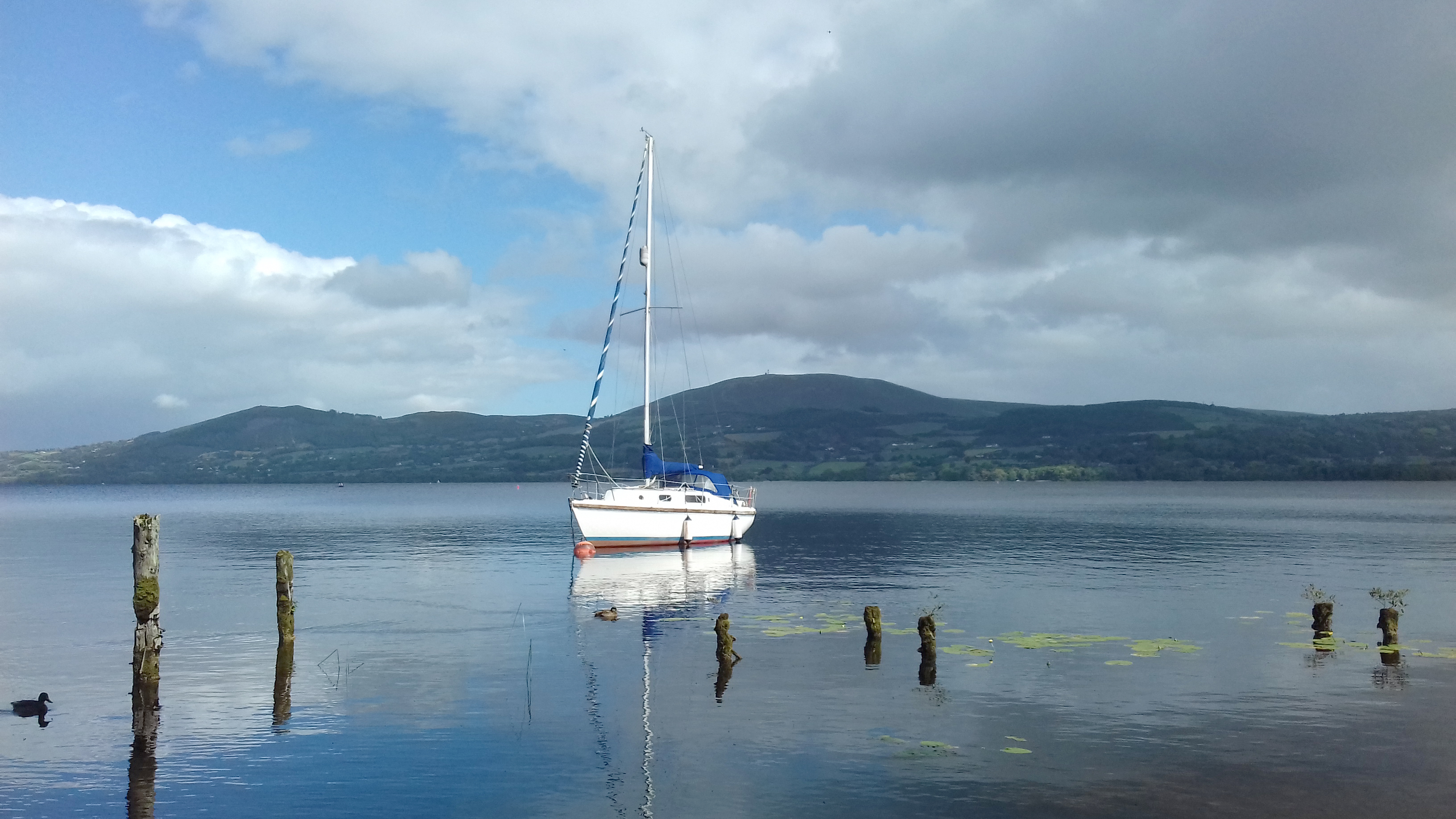 Lough Derg with a lone sail boat and a soft Arra Mountains in the background