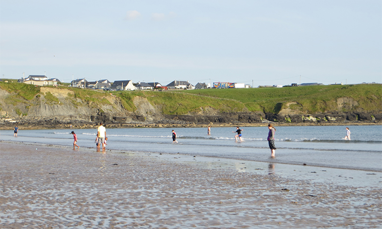 Lahinch beach with people paddling